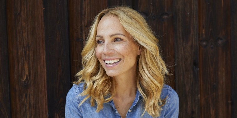 Happy blond woman in front of wooden wall