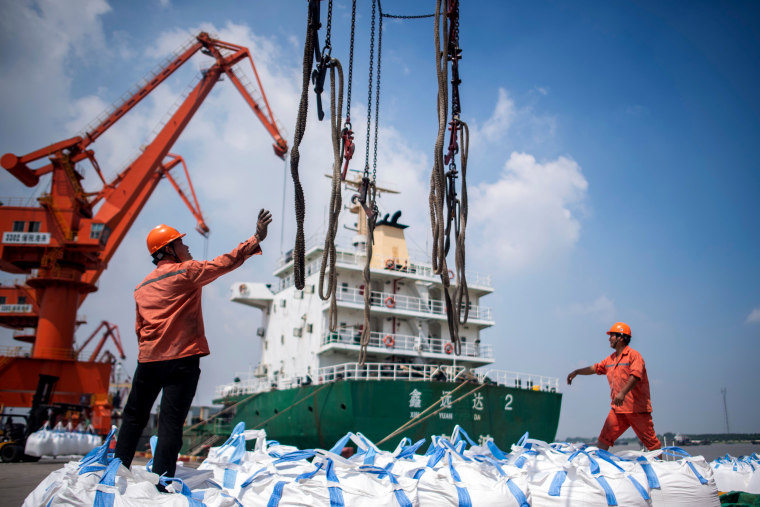 Image: Workers unload bags of chemicals at a port in China's eastern Jiangsu province on Aug. 7, 2018.