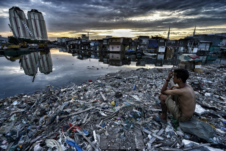 Image: A man sits on the ruins of what was the neighborhood of Pasar Ikan in Jakarta, Indonesia.