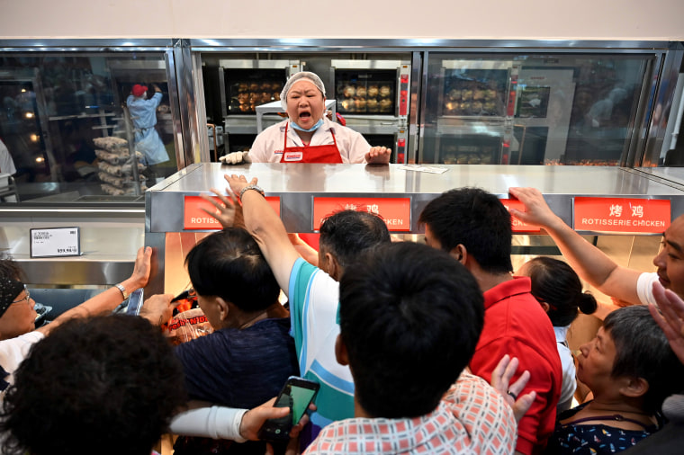 Image: People try to get a roast chicken at the first Costco outlet in China, on the stores opening day in Shanghai on Aug. 27, 2019.