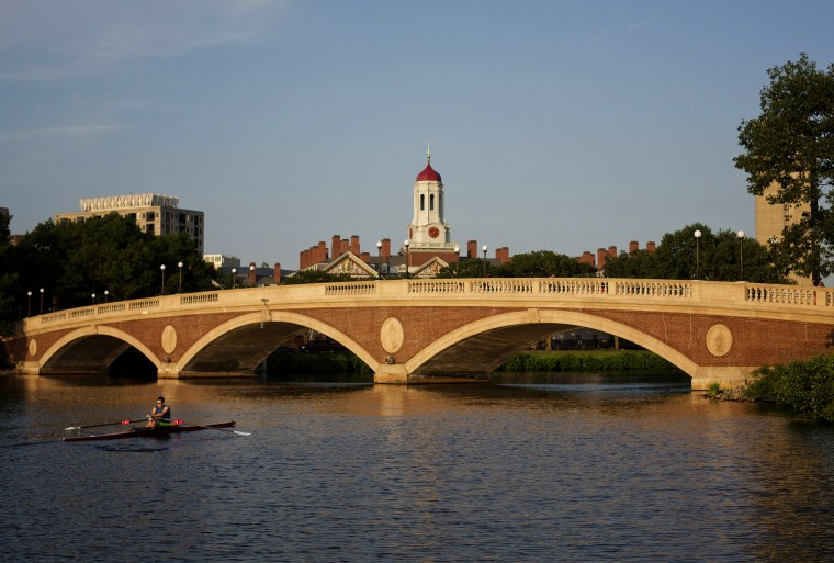 Image: A sculler rows on the Charles River past the Harvard University campus in Cambridge, Mass., on June 30, 2015.