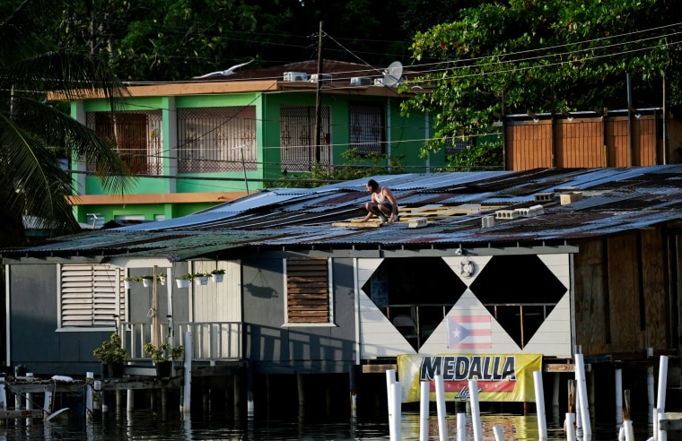 Image: A man fixes a tin roof on a house in Cabo Rojo as Tropical Storm Dorian approaches Puerto Rico on Aug. 27, 2019.