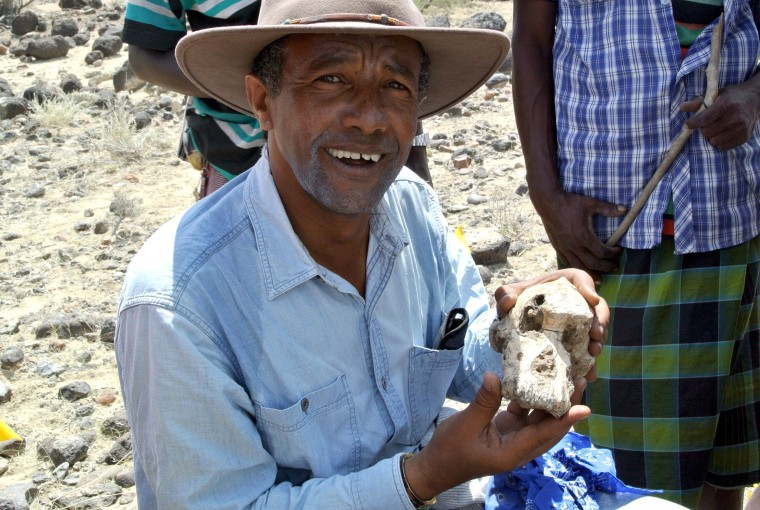 Image: Yohannes Haile-Selassie posing with a fragment of Australopithecus skull in Ethiopia.