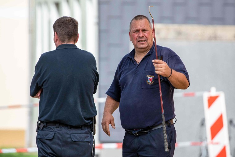 Image: Snake experts at work in front of a residential building in Herne, western Germany, where a deadly cobra was on the loose.