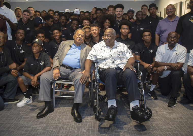 Andrew Young, left, and Hank Aaron, right, pose for photos with the participants at the end of the Hank Aaron Invitational at SunTrust Park in Atlanta on Aug. 2, 2019.