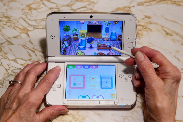 Image: Audrey Buchanan, 88, plays Animal Crossing on her pink Nintendo 3DS XL
