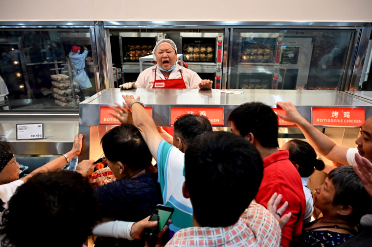 Image: People try to buy roast chicken at the opening of the first Costco in Shanghai, China, on Aug. 27. 2019.