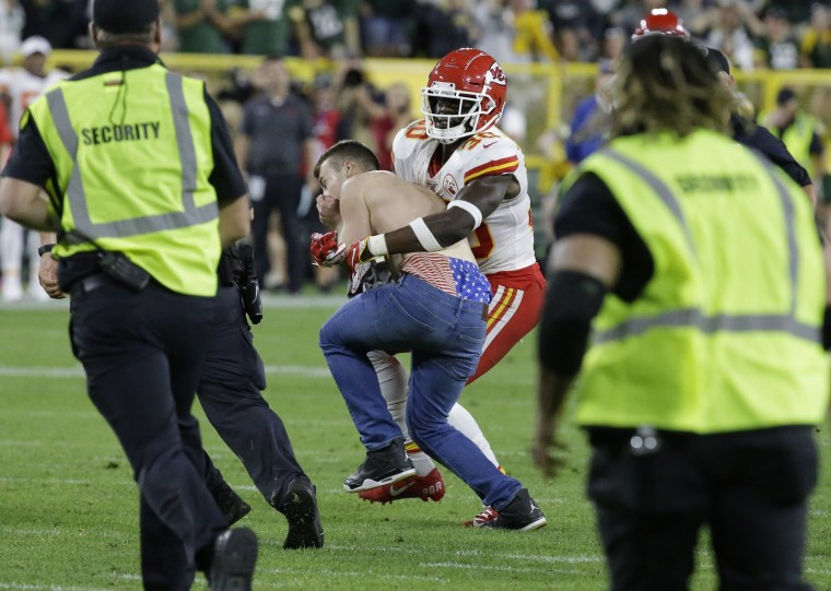 Image: Kansas City Chiefs' Harold Jones-Quartey tackles a fan that ran on the field during the second half of a preseason NFL football game against the Green Bay Packers