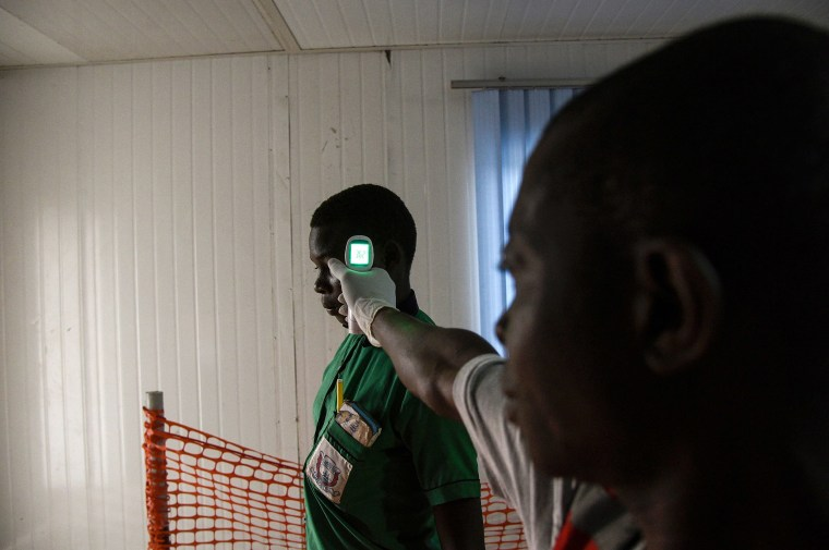 Image: A health official checks the temperature of a school going pupil from the Democratic Republic of Congo (DRC) at the Mpondwe border point, separating Uganda and the DRC, as he walks through the computerised Mpondwe Health Screening Facility