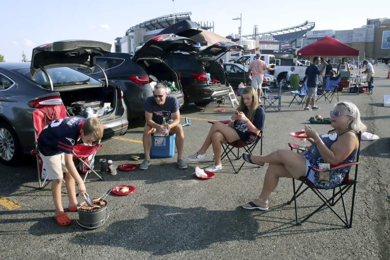 Shea Schuster, of Worcester, Mass., grills kielbasa while tailgating with his family in the parking lot of Gillette Stadium before an NFL preseason football game between the New England Patriots and the Carolina Panthers Aug. 22, 2019, in Foxborough, Mass.