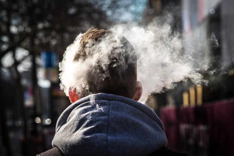DEU Deutschland Germany Berlin Der Rauch einer E-Zigarette umh?llt den Kopf eines Mannes auf dem Kudamm.
