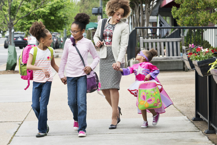 Image: Mixed Race woman walking daughters to school in city