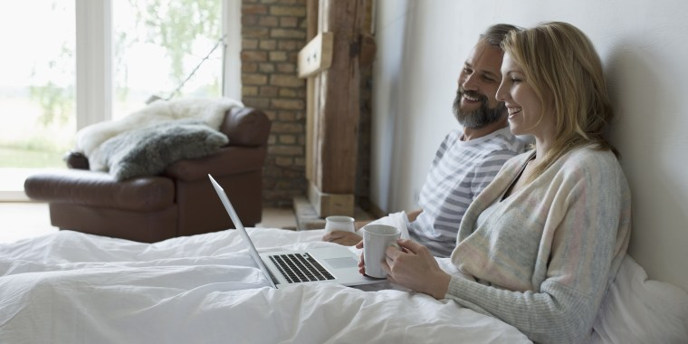 Couple drinking coffee and using laptop in bed