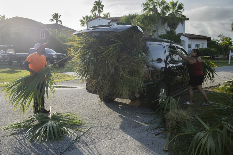 Victoria Casanova and Arryngton Turner stuff palm fronds into the back of their Midsize SUV. The couple, once local residents, drove down from Georgia as part of their tree trimming business to cut back palm fronds, which many worry will become projectiles that can cause damage to buildings and people during Hurricane Dorian.