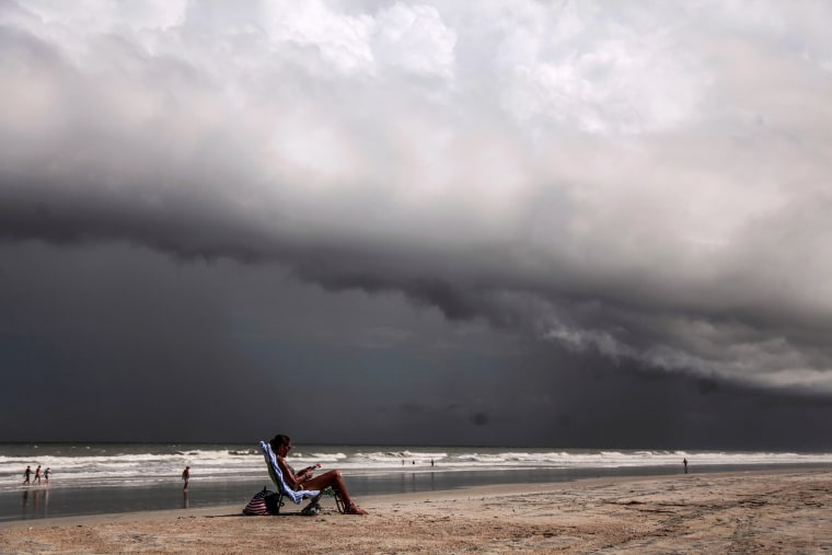 Image: Tricia Cheshire, a resident of Amelia Island sunbathes for the last few minutes before storms hit the coast before Hurricane Dorian in Jacksonville, Florida,