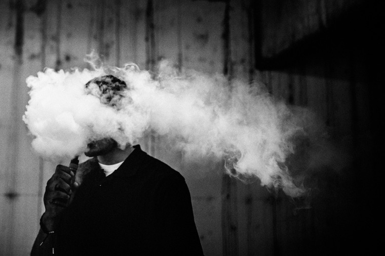 Image: A young man vapes.