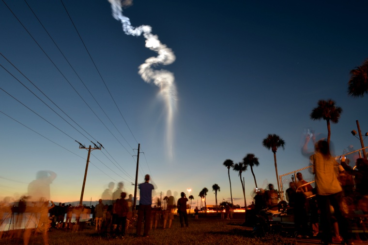 Image: People watch the Atlas V rocket launch at Cape Canaveral Air Force Station in Fla., on Aug. 8, 2019. Atlas V carries an Advanced Extremely High Frequency communications satellite for the Air Force Space and Missile Systems Center.