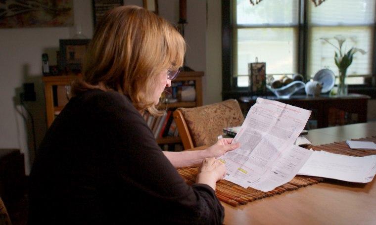 Image: Suzanne Luttig looks over medical bills.