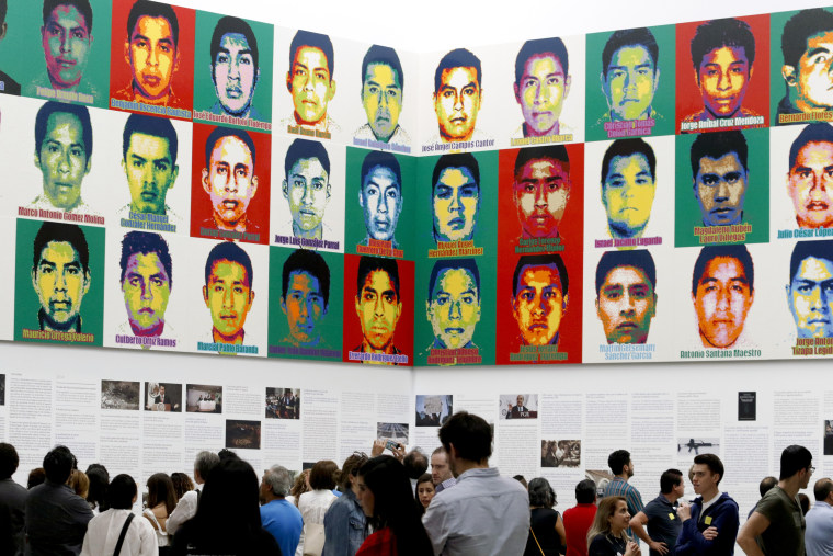Image: People stand under portraits of 43 college students as part of an art installation by Ai Weiwei at the Contemporary Art University Museum in Mexico City on April 13, 2019.
