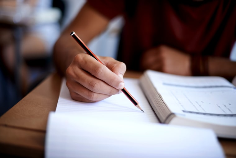 Image: Closeup shot of a young man writing on a note pad