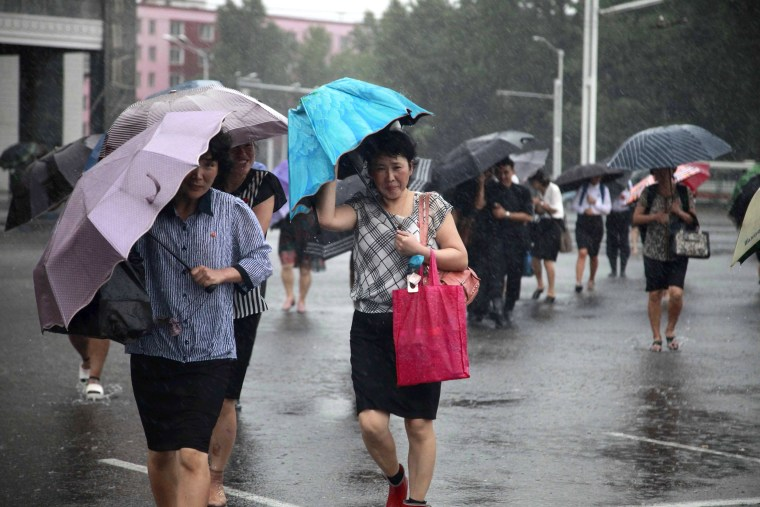 Image: Pedestrians shield themselves from wind and rain from Typhoon Lingling in Pyongyang, North Korea, on Sept. 7, 2019.