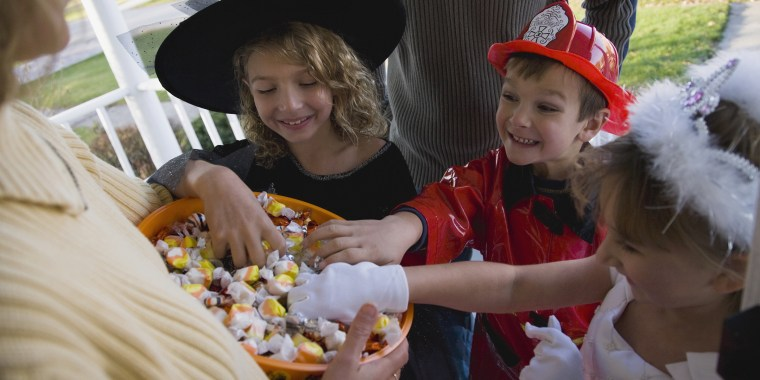 Children in Halloween costumes reaching into bowl of candy