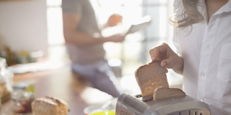 Woman putting bread in toaster