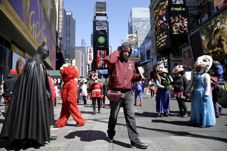 A bus tour ticket seller, center, walks through a group of costumed characters in Times Square in New York on March 29, 2016.