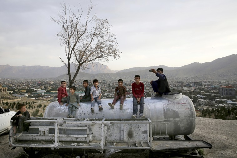 Image: A group of Afghan boys sit on the water tank over looking Kabul, Afghanistan on Aug. 23, 2019.