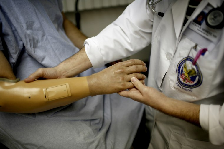 Image: A doctor checks a patients prosthetic arm at the Veterans Affairs hospital in San Diego, Calif., in 2007.