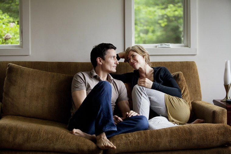 Image: Couple sitting on sofa at home