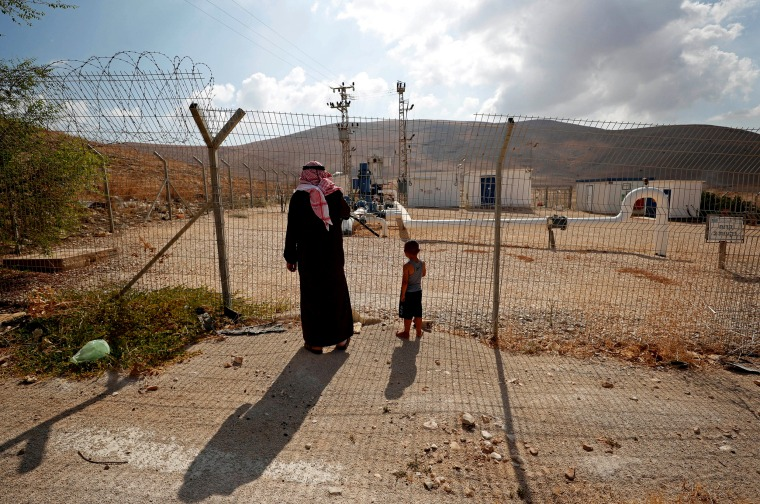 Image: Palestinians stand at a fence separating the Jordan Valley and the Israeli-occupied West Bank on Aug. 21, 2019.