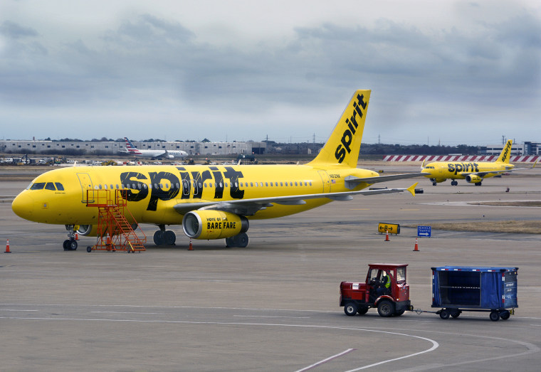 A Spirit Airlines plane is parked on the tarmac at Dallas/Fort Worth International Airport