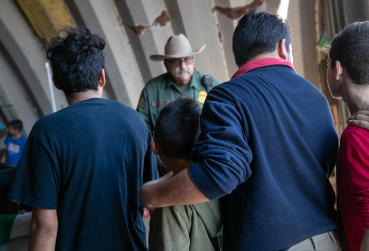 Image: A U.S. Border Patrol agent speaks with families, mostly from Central America, who had crossed the Rio Grande from Mexico and presented themselves to agents