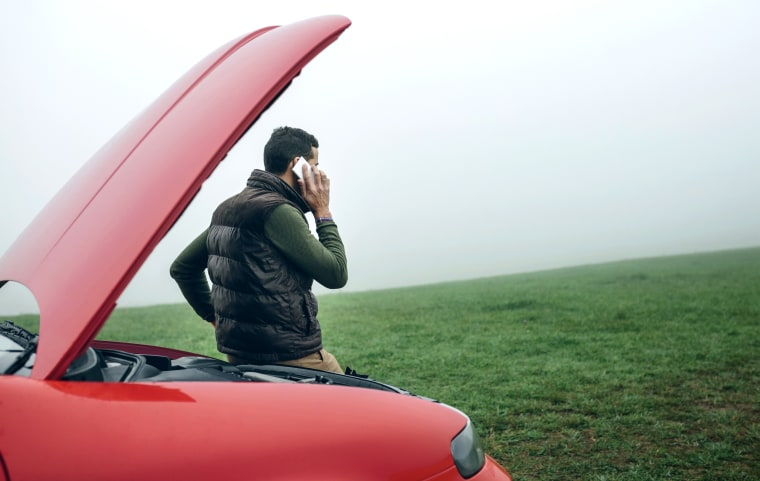 Image: Man talking on cell phone next to broken car