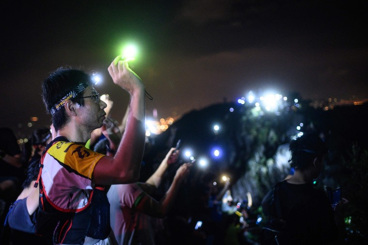 Image: A protester lights up a laser beam at the hill top of Lion Rock in Hong Kong