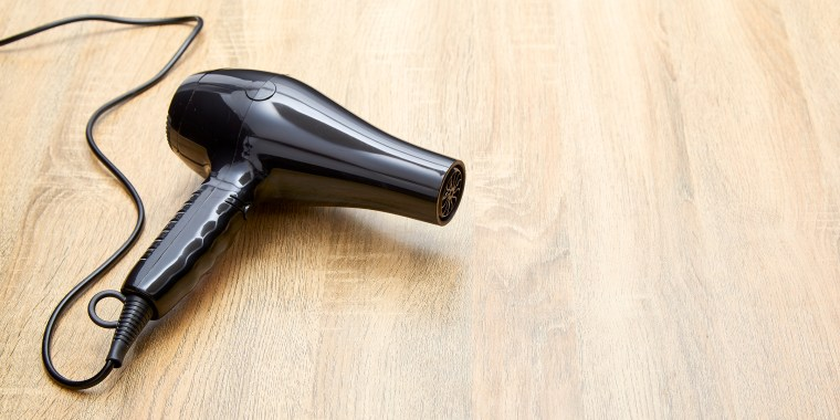 High Angle View Of Hair Dryer On Wooden Table