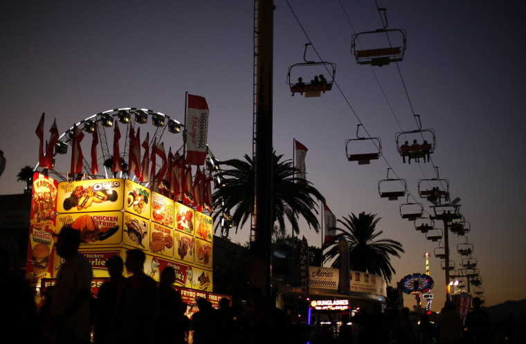 Image: People walk in front of a deep fried food stand at sunset at the Los Angeles County Fair in Pomona