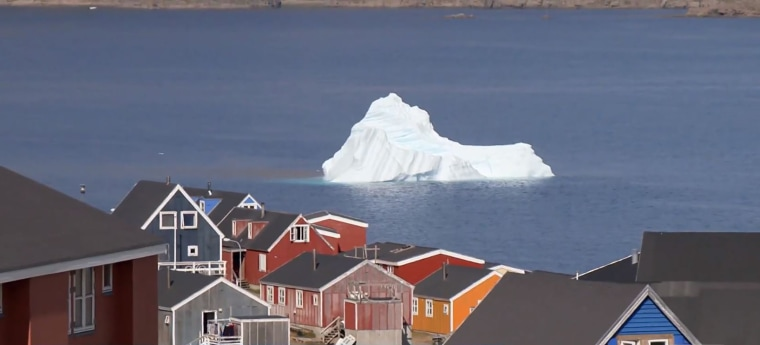 An iceberg floats past a village in Greenland.