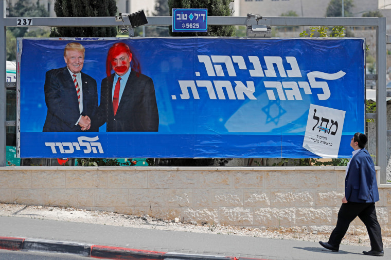 Image: An Israeli man looks at a defaced election billboard for the Likud party showing US President Donald Trump (L) shaking hands with Likud chairman and Prime Minister Benjamin Netanyahu in Jerusalem