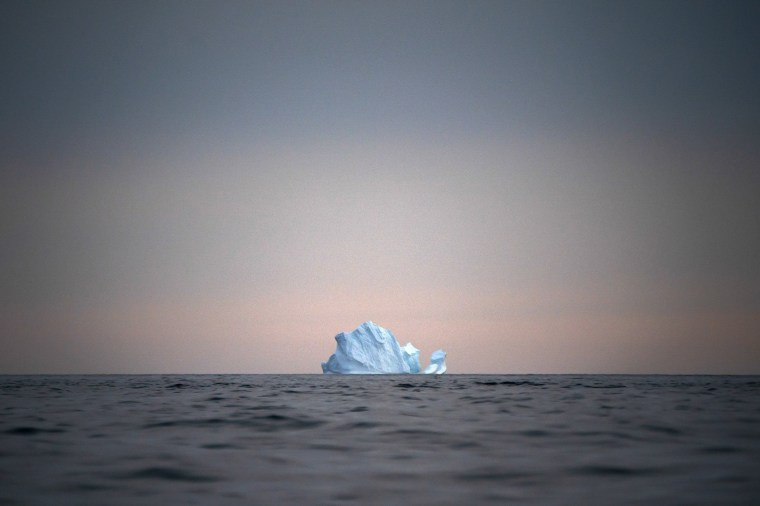 Image: A large Iceberg floats away as the sun sets near Kulusuk, Greenland