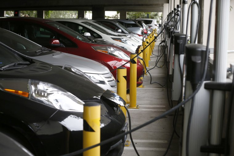 Electric cars sit charging in a parking garage at the University of California, Irvine