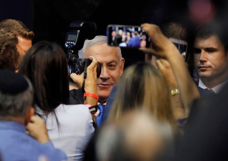 Image: Israeli Prime Minister Benjamin Netanyahu is confronted by the press as he arrives to address supporters at his Likud party's electoral campaign headquarters in the coastal city of Tel Aviv