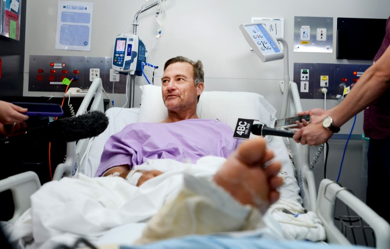 Image: Neil Parker speaks to reporters from his hospital bed while recovering after he crawled through Australian woodland for two days with a broken leg and arm on Sept. 18, 2019.