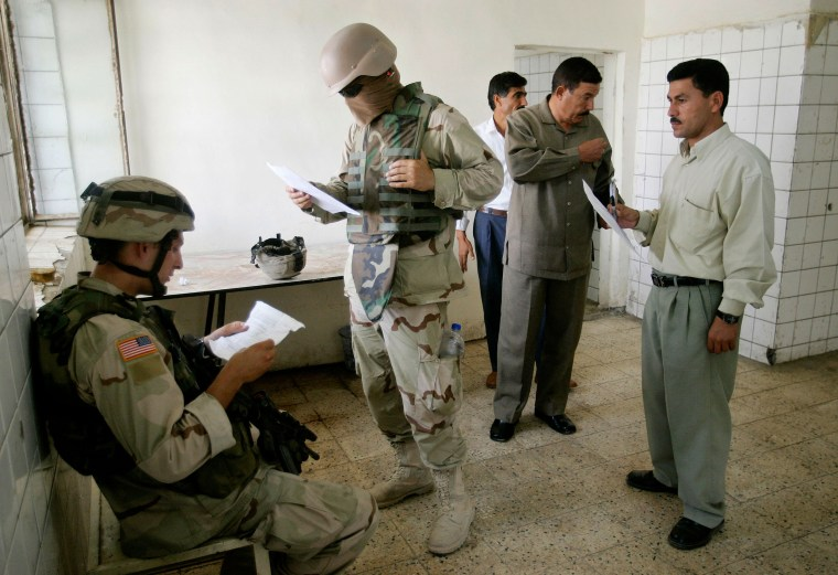 US soldier checks workers' list during a patrol in Arij, northern Iraq.
