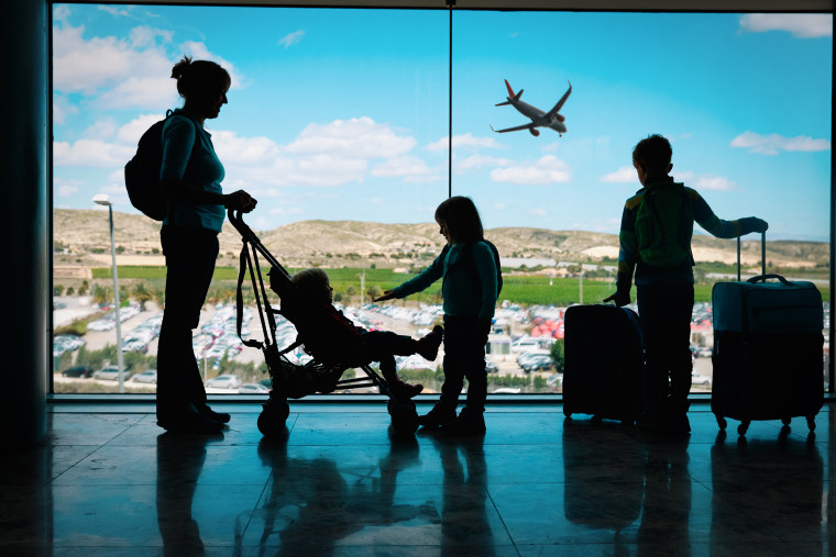 Image: mother with kids and luggage looking at planes in airport