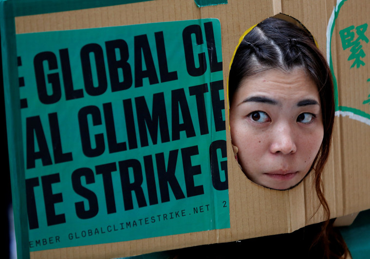 Image: A woman puts her face out of a banner at an event to mark the day of global climate strikes in Tokyo