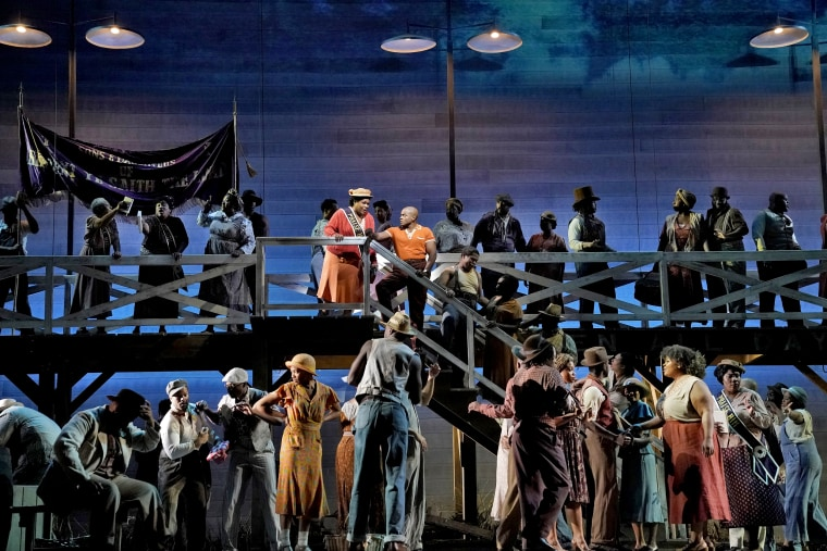 """Image: Latonia Moore, center left on stairs, and Frederick Ballentine in a scene from Gershwins' """"Porgy and Bess"""" at the Metropolitan Opera."""