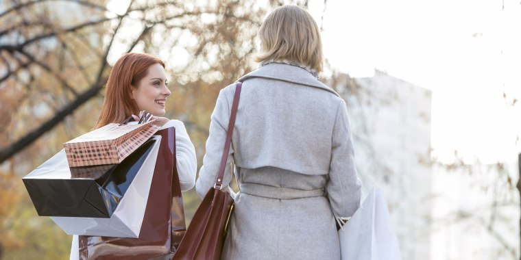 Women carrying shopping bags in city park