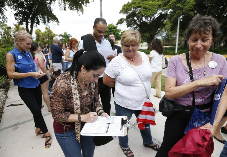 Image: A woman fills out a new voter registration form
